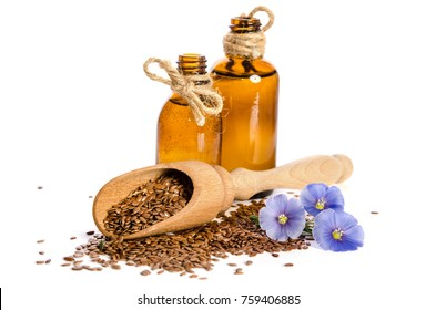 Flax seeds in the wooden scoop, bottle with oil and  beauty flowers isolated on white background. Phytotherapy.
