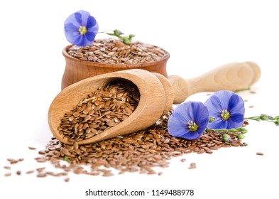 Flax seeds in the wooden scoop and bowl, beauty flowers isolated on white background.
