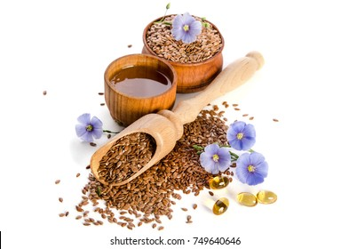 Flax seeds in the wooden scoop, bowl with oil and oil in caps and  beauty flowers isolated on white background. Phytotherapy.