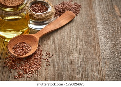 Flax seeds and a wooden spoon with bottle of oil on a wooden table. Healthy food and drink concept.