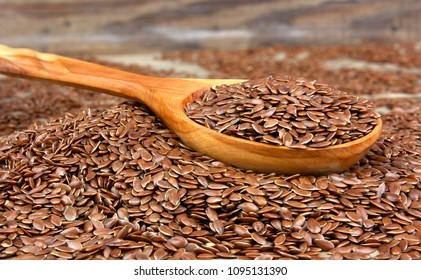 Flax seeds in wooden spoon on wooden background. 
