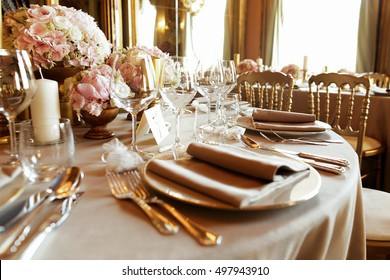 Flax serviettes lie over shiny plates on rich dinner table