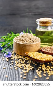 Flaxseed flour in a bowl, white and brown seeds in spoons and on table, flax leaves and flowers, oil in a glass jar on wooden board background