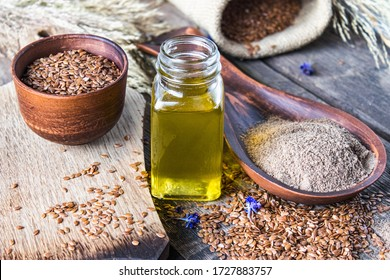 Flaxseed oil in a bottle near the chopped flax seeds in a spoon. Flaxseed oil is used in cooking, medicine, cosmetology.