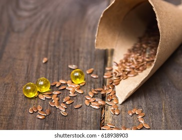 Flaxseed oil in caps on a wooden background. Phytotherapy. Linum usitatissimum oil. Homeopathy. Line seed oil. Alternative medicine.