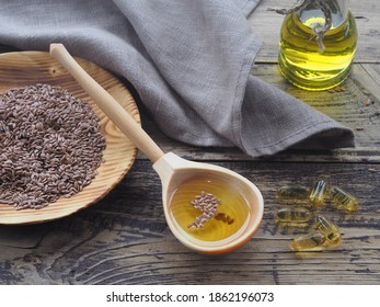 Flaxseed oil in a wooden spoon, linseeds in a wooden plate, oil in capsules with a linen napkin on a dark wooden table, top view. Natural healthy oleum lini with omega and vitamins