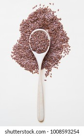 Flaxseeds on wooden spoon on beige background Top view.
