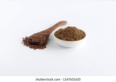 Flaxseeds and their powder, which are healthy food and contains, among others, omega-3 fatty acids and lignans, on a wooden spoon and in a bowl.