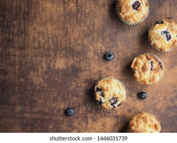 Flay lay of crumble blueberry muffins on wooden table