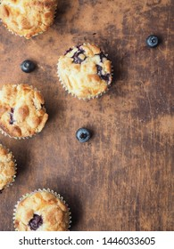 Flay lay of crumble blueberry muffins on wooden background