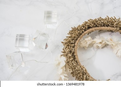 Flay lay image of crystal cubes with flower band on marble background