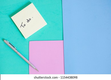 Flay lay of pen and post it note reminder to do list against bright colorful background with blank copy space