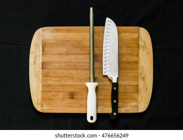 Flay lay photo of a knife sharpener (honing steel) and a chefâ??s knife on a cutting board against black background