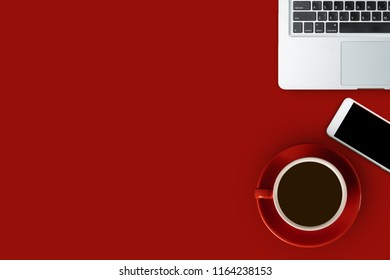 Flay lay red desk with laptop, smartphone and a red cup of black coffee, top view with copy space