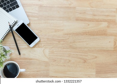 Flay lay, Top view office table desk with smartphone, laptop, coffee, pencil with copy space wood background.