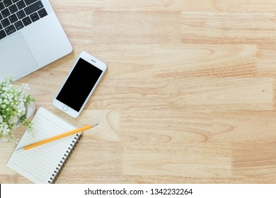 Flay lay, Top view office table desk with smartphone, keyboard, laptop, pencil, notebook, leaves with copy space background.