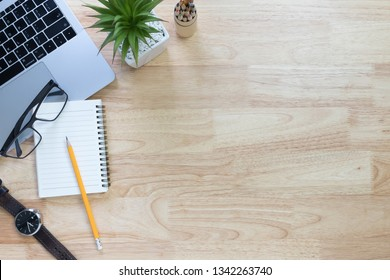 Flay lay, Top view office table desk with laptop, notebook, glasses, watch, pencil, leaves with copy space wood background.