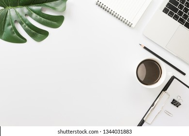 Flay lay, Top view office table desk with laptop, sheet, notebook, keyboard, coffee, pencil, leaves with copy space white background.