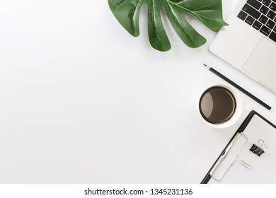 Flay lay, Top view office table desk with laptop, sheet, keyboard, coffee, pencil, leaves with copy space white background.