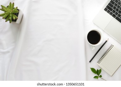 Flay lay, Top view office table desk with notebook, laptop, keyboard, coffee, pencil, leaves with copy space white background.