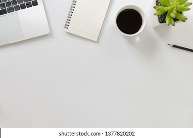 Flay lay, Top view office table desk with laptop, notebook, keyboard, coffee, pencil, leaves with copy space white background.