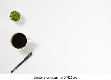 Flay lay, Top view office table white desk with coffee, pen, vase with copy space background. minimal desk.