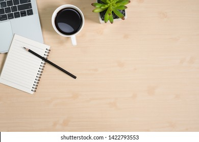 Flay lay, Top view office table wood desk with laptop, notepad, coffee, pencil, leaves with copy space background.
