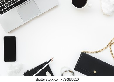 Flay Layout with Laptop and Feminine Items in Black and Gold Tones on a White Background with Coffee, Phone, Handbag, and Notebook, and Room for Copy