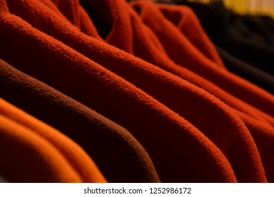 fleece jackets hanging in row at store, colorful polar fleece jackets on a hanger macro shot made of recycled plastic bottles