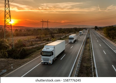 Fleet of blue lorry trucks on a country highway under an amazing orange sunset sky