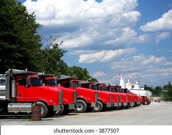 Fleet of bright red trucks in industrial yard