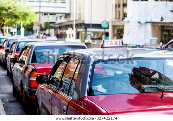 """A fleet of Hong Kong taxis waiting at a taxi stand. Hong Kong taxis are easily recognizable by their red and white colors. The generic Chinese text on the cab's roof and body translates to """"Taxi""""."""