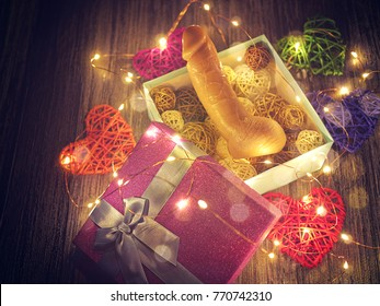 A flesh-colored dildo is in an open gift box. Around are wicker hearts of different colors and a luminous garland. Romantic background for Valentine's day or love card