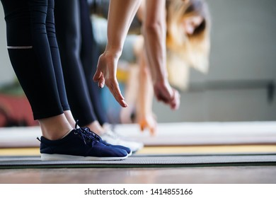 Flexibility, activity, yoga, pilates, warming up concept. Women hands stretching to toecaps on group workout