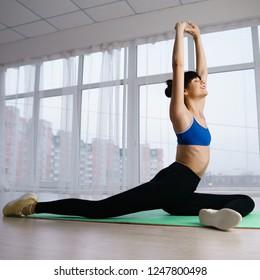 Flexibility, grace, good mood, healthy lifestyle,vitality, yoga. Pilates workout for women. Sporty lady stretching in yoga studio