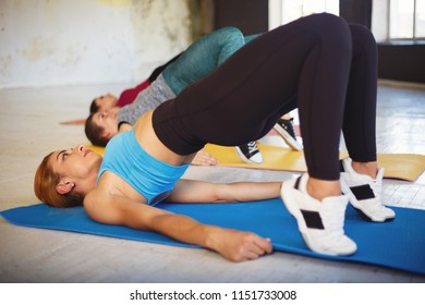 Flexibility, health, good mood, active lifestyle, workout, harmony. Group of fit sporty women practicing yoga in fitness gym doing bridge plank exercise