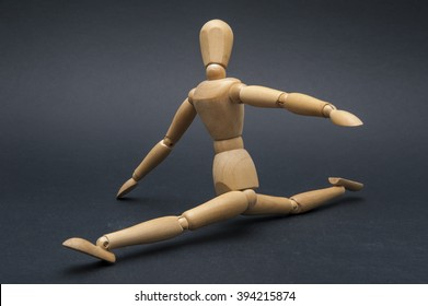 Flexibility/Person represented by a wooden dummy performing the splits and showing how flexible he is.