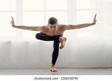 Flexible athletic man doing yoga asana at home