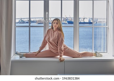 Flexible cheerleader trains at home, she does splits on windowsill, demonstrating good stretching.