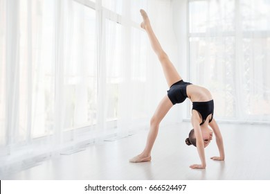 Flexible child, beautiful little gymnast girl doing gymnastic exercises or exercising in fitness class, white background. Sport, training, fitness,stretching, yoga, active lifestyle concept