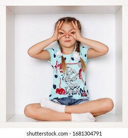 Flexible child sits in a white box and plays a different