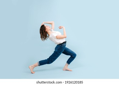 Flexible contemporary dancer poses in front of blue studio background. Her legs in a lunge, arching herself back.