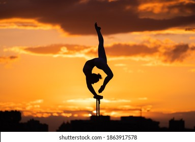 Flexible female circus Artis keep balance and doing contortion on the rooftop against dramatic sunset and cityscape. Handstand and equilibrium concept