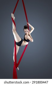 Flexible female gymnast performing aerial exercise