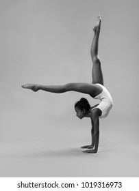 Flexible girl in white leotard. Black and white photo.