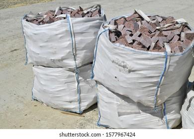 A flexible intermediate bulk container (FIBC) with granite blocky on a construction site.