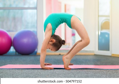 Flexible little girl gymnast doing a bridge in gym. Sport, training, fitness, yoga, active lifestyle concept