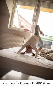 Flexible.  Little girl on bed.