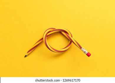 Flexible pencil . Isolated on yellow background.