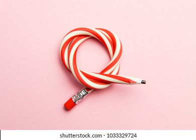 Flexible pencil on a pink background. Bent pencils two-color.